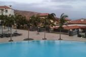 jeden z hotelových bazénů s palmami zmítanými větrem
