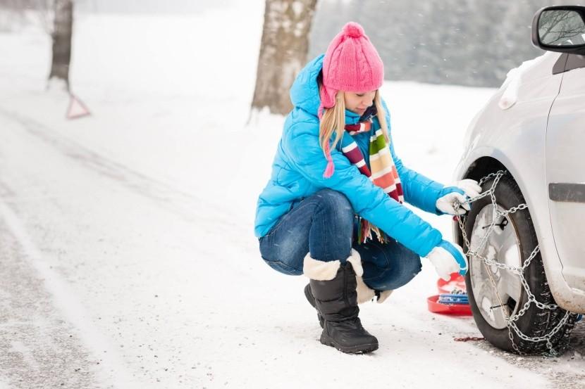 Žena nasadzujúca snehové reťaze